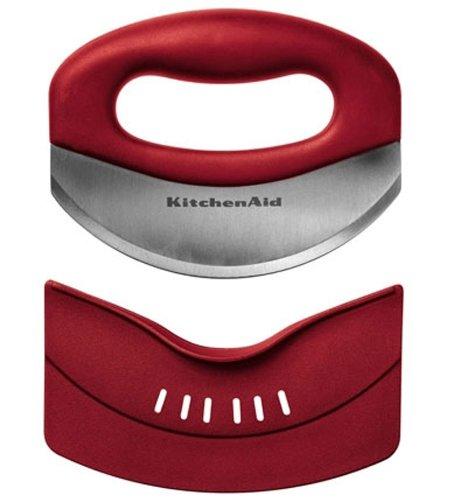 Мезалуна (нож для зелени) красная, KC173OHERA, KitchenAidКухонные инструменты<br>Быстро и эффективно измельчить большое количество зелени вам поможет специальный нож – мезалуна. Его изогнутое лезвие аккуратно нарежет не только петрушку, укроп, зеленый лук или базилик, но и измельчит орехи, пармезан, шоколад или пряности. Работать с ножом просто и совершенно безопасно. Ваши руки надежно защищены, а для хранения имеется специальный футляр.&#13;<br>Функциональныеи прочные, кухонные аксессуары от KitchenAid станут для вас верными помощниками. Торговая марка KitchenAid предлагает вам большой выбор кухонных аксессуаров, в числе которых - разнообразные лопатки, овощечистки, венчики, консервные ножи и т.п. Великолепный комплект, состоящий из ультрасовременных профессиональных гаджетов, будет прекрасным дополнительным аккордом для планетарного миксера Китченэйд.&#13;<br>Каждый стальной/силиконовый аксессуар разработан для неутомимых энтузиастов кулинарии и творчества, стремящихся достичь в своем деле идеального результата. Оригинальный дизайн утвари и приспособлений полностью отвечает стилистике всей линейки бытовой техники от KitchenAid. Практичные аксессуары изготавливают из нержавеющей стали и покрывают их жаростойким силиконом, выдерживающим температуру до +260° С. Аксессуары из силикона – наилучшее решение для кухни, ведь они подходят для посуды любого вида, в том числе – для антипригарной.&#13;<br><br>