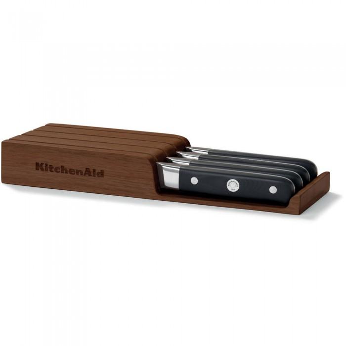 Набор ножей для стейков, 4 шт., подставка из акации, KKFTR04SKWM, KitchenAidНожи и наборы ножей<br>Набор из 4 ножей для стейков включает подставку для горизонтального хранения из акации. Деревянная подставка выглядит стильно и солидно, а также оберегает ножи от повреждений и позволяет надолго сохранить остроту заточки.&#13;<br>Особенности:&#13;<br>Рукоятка с тремя креплениями&#13;<br>Ручки ножей KitchenAid изготовлены из спрессованного под высоким давлением непористого композитного материала, что делает их невероятно прочными. Эргономичная форма рукоятки и тщательно выверенный баланс лезвия обеспечивают полный контроль над инструментом и удобный захват. Завершающий этап обработки рукоятки производится вручную. Именно поэтому ножи KitchenAid выглядят также восхитительно, как и работают.&#13;<br>Лезвие, закаленное экстремальным холодом&#13;<br>Лезвие каждого ножа проходит этап закаливания ультранизкими температурами. При этом молекулярная структура металла изменяется, лезвие становится более прочным, гибким и функциональным. Такая сталь лучше сохраняет заточку, то есть ваш нож будет острым как бритва еще дольше. Благодаря высокой гибкости металла, ножи KitchenAid реже ломаются. &#13;<br>Крепления из ювелирной стали&#13;<br>Отполированные до зеркального блеска стальные заклепки, украшающие рукоятки ножей, обеспечивают прочное крепление и полное отсутствие зазоров. Центральная заклепка немного больше остальных, для более прочного крепления. На её поверхность нанесен фирменный логотип KitchenAid, подтверждающий аутентичное качество изделия. Одно из замечательных преимуществ ювелирной стали состоит в том, что полированная поверхность креплений всегда остается сверкающей. По этой причине ваши ножи на долгие годы сохранят свой потрясающий внешний вид. &#13;<br>Нержавеющая сталь&#13;<br>Ножи изготовлены из высококачественной немецкой нержавеющей стали марки 1.4116. Этот сплав устойчив к коррозии и появлению пятен.&#13;<br>Подходит для посудомоечной машины&#13;<br>Ножи Kitche